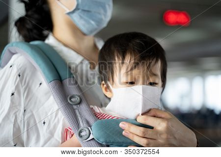 Asian baby with mother in baby carry,both wearing a protection mask against air pollution and corona virus,mother ensure baby wearing mask well before flight in Don Muang airport area,BangkokThailand.