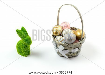 Easter Egg Background With Golden Shine Decorated Eggs In Basket And Green Bunny Isolated On White.
