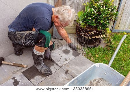 A Grey Haired Male Retiree Laying Paving Stones In His Own Backyard As A Weekend Project