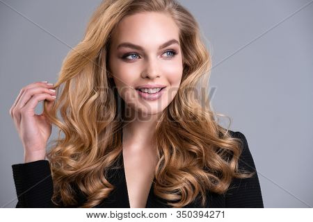 Beautiful face of an attractive model with blue eyes. Smiling Woman with long brown hair and natural makeup. Closeup portrait of a caucasian female. Happy young woman. Beauty face of a blonde