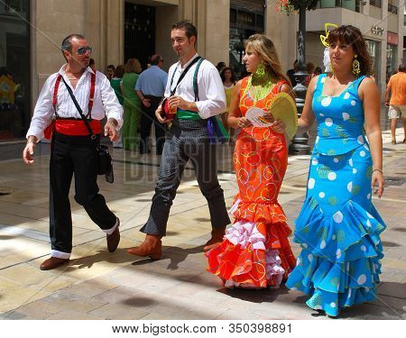 Malaga, Spain - August 18, 2008 - Men And Women In Traditional Dress Walking Along Calle Marques De