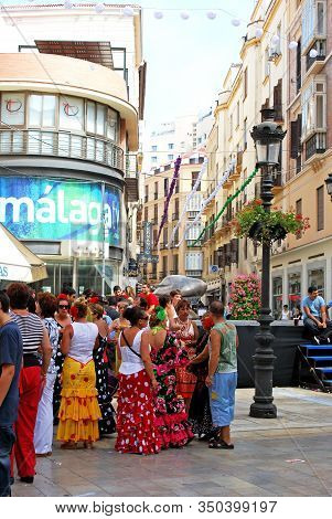 Malaga, Spain - August 18, 2008 - Women In Flamenco Dresses Along Calle Marques De Larios At The Fer