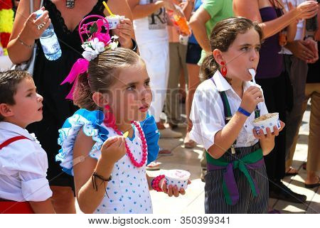 Malaga, Spain - August 18, 2008 - Children In Traditional Dress Eating Ice-cream Along Calle Marques