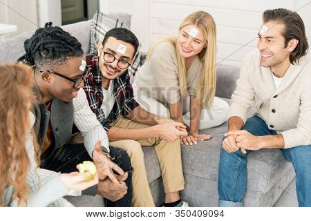 Group of happy friends sitting together o sofa playing Guess Who game, high angle shot