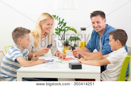 Happy Young Family Playing Card Game At Dining Table At Bright Modern Home.