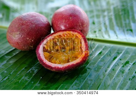 Collection Of Whole And Cut Passion Fruits (maracuya) Isolated On Banana Leaf. Passion Fruit Smoothi