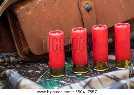 Close-up View Of Old Leather Cartridge Belt And Red Shotgun Shells On The Camouflage Background