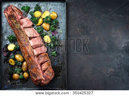Barbecue dry aged venison tenderloin fillet steak and saddle natural with kalette and fried potatoes offered as top view on a rustic board with copy space right