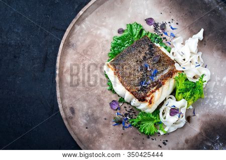 Gourmet fried European skrei cod fish filet with rapini broccoli rabe and noodles as top view on a modern design plate with copy space left