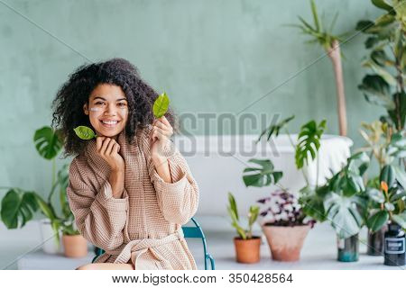 Beauty Portrait Of Mixed Race Woman Sitting In Bathroom Holding Lemon Tree Leaves With Green Plants