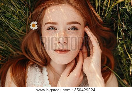 Beautiful Positive Tranquil Ginger Teen Girl With Daisy Flower In Hair Lying On Green Grass And Look