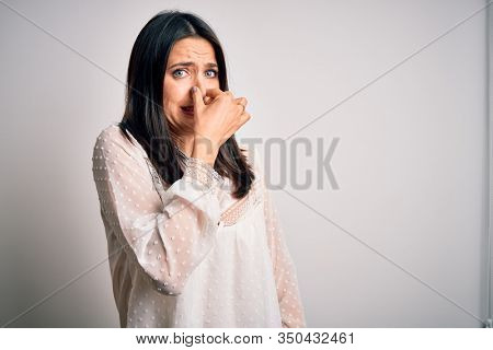 Young brunette woman with blue eyes wearing casual t-shirt over isolated white background smelling something stinky and disgusting, intolerable smell, holding breath with fingers on nose. Bad smell