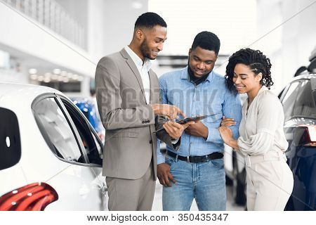 Car Rent. Afro Salesman Offering Couple Automobile Standing In Auto Rental Office.