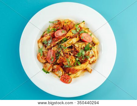 Penne Pasta With A Rich Tomato Sauce And Slices Of British Pork Sausage Topped With Cheddar Cheese