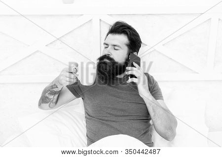 Pleasant Conversation. Good Morning. Hello Dear. Bearded Man Using Mobile Technology In Bed. Handsom