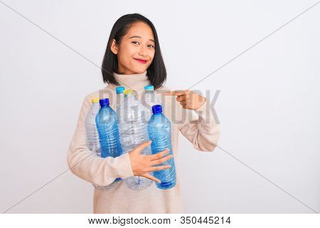 Young beautiful chinese woman recycling plastic bottles over isolated white background with surprise face pointing finger to himself