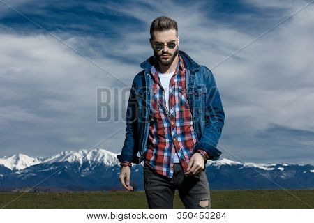 Tough man while wearing jeans jacket and sunglasses, moving on outdoor nature background