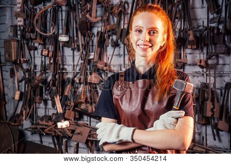 Redhaired Ginger Young European Feminist Woman Wearing Leather Apron Working Blacksmith Workshop.sma