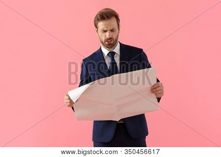 Bothered businessman reading a newspaper and frowning while standing on pink studio background