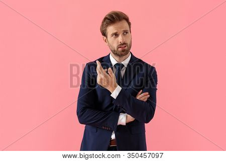 Bothered businessman talking and explaining, gesturing with his hands crossed while standing on pink studio background