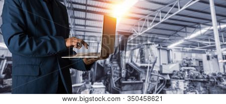 Manager Industrial Engineer In The Suit Uses Laptop Computer With The Background Industry Manufactur