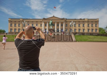 People Visiting And Enjoying The Royal Palace And Statue Of King Karl Johan Xiv In Oslo, Norway