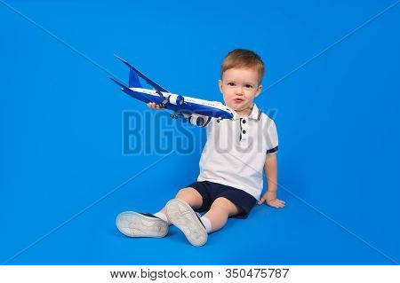 Happy Child Sits Holding Plane In His Hand And Imagining How He Is Flying On Plane On Blue Backgroun