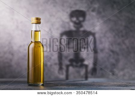 A Bottle Of Whiskey With A Shadow In The Shape Of A Skeleton. Concept On The Harm Of Alcohol And Har