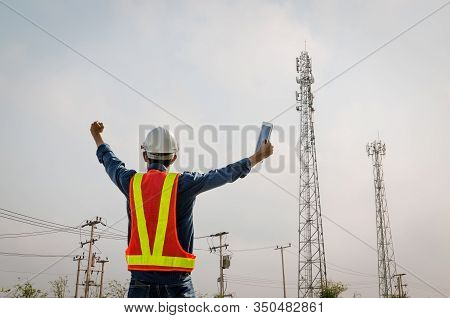 Successful Male Engineer Stands At The Background Of The Communication Tower