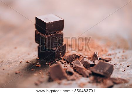 Chopped Dark Chocolate With Cocoa On Wooden Table, Selected Focus, Close Up Photo.