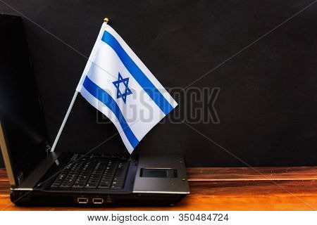 Flag Of Israel , Computer, Laptop On Table And Dark Background