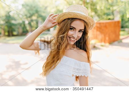 Close-up Portrait Of Inspired Young Lady With Beautiful Eyes Holding Straw Hat. Romantic Fair-haired