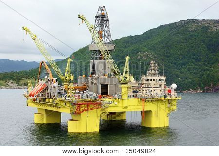 Ocean offshore oil rig drilling platform off near wooded shore of Stavanger, Norway.