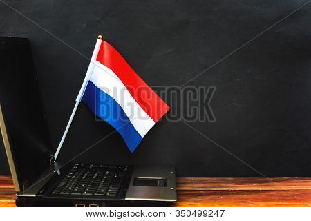 Flag Of Netherlands , Computer, Laptop On Table And Dark Background