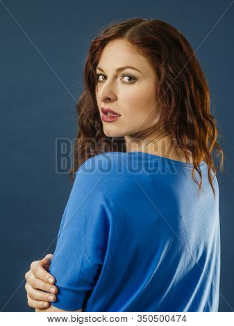Portrait Of A Beautiful Redhead Turning Around And Looking, Over Blue Background.