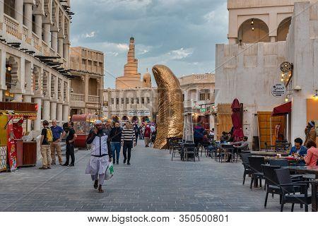 Doha,qatar-february 10,2020: Souk Waqif Doha, Qatar Main Street Daylight View  With The Thumb Monume