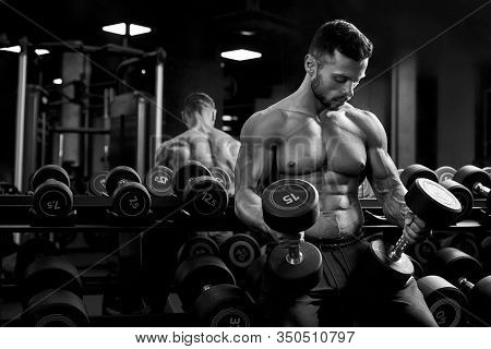Front View Of Shirtless Male Bodybuilder Holding Weights In Arms On Thighs. Sportsman With Perfect M