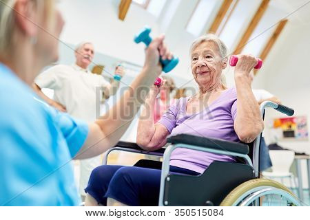 Senior woman in wheelchair doing rehab workout with dumbbells after stroke