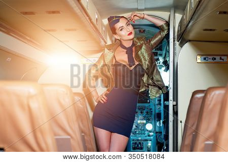 Stewardess And Travel Time. Beautiful Flight Attendant In An Airplane Cabin Smiling. Stewardess Dres