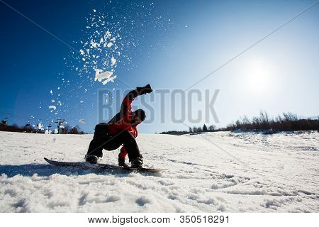 Man On A Snowboard Falling Down On Snow