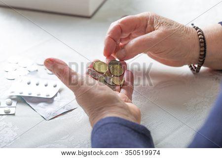 An Elderly Woman Pensioner Counts Ukrainian Coins Money. Poor Pensioner