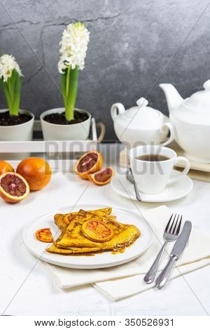 Spring Serving Breakfast For One Person. On The White Table Are Plate With A Crepe Suzette, Fork, Kn