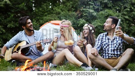 Group Of Friends Camping And Sitting Around Camp Fire
