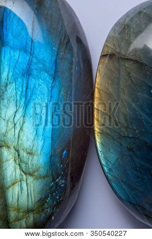 Two Green Blue And Yellow Rounded Labradorite Crystal Stone Isolated On Light Background