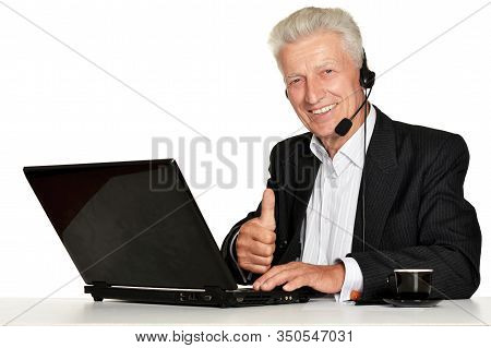 Old Businessman In Headphones Working With Laptop Isolated