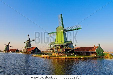 Old Dutch Windmills At Zaan River In Setting Sun At Zaanse Schans, Netherlands At Spring.