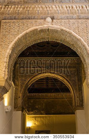 SEVILLE, SPAIN - December 09 2019: Ornamented decorations of the arches inside the Royal Alcazars of Seville palace, Spain. Famous Andalusian architecture