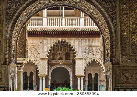 SEVILLE, SPAIN - December 09 2019: View through an arch of Patio de las Doncellas or Hall of the Maidens in the Real Alcazar, Seville, Spain, a UNESCO World Heritage Site