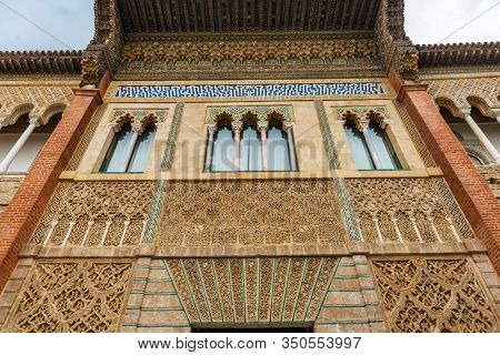 SEVILLE, SPAIN - December 09 2019: Moorish windows in Patio de la Monteria courtyard in the Real Alcazar in Seville Spain looking up from below with decorative frieze, a Unesco World Heritage Site