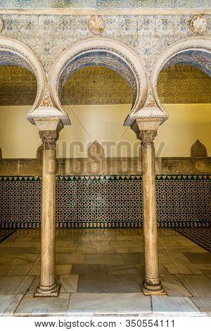 SEVILLE, SPAIN - December 09 2019: Detail of a beautifully entrance anr ornate tiled arch into a room of the real alcazar palace in the spanish city sevilla.